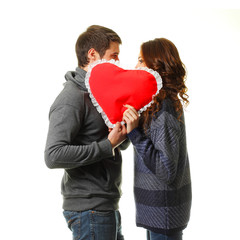 Two young dates kissing behind heart.