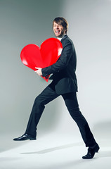 Cheerful young man holding big heart