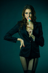 sexy girl in a jacket, stockings and bra sucks a lollipop