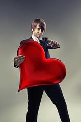 Handsome boy holding a cartoon heart