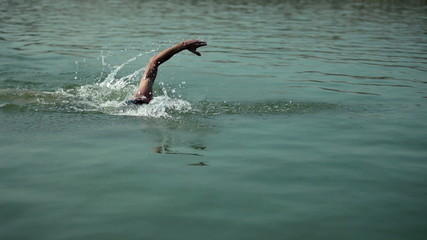 Middle shot of man swimming in cold river