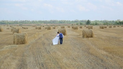 Bride and groom walking on the field in which the haystacks