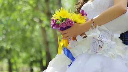 The bride holds a wedding bouquet, groom hugging her waist