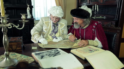 Mayor and scholar in medieval clothes talking about an old open map