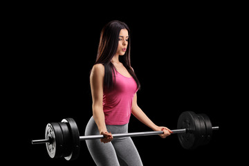 Beautiful young woman exercising with a barbell