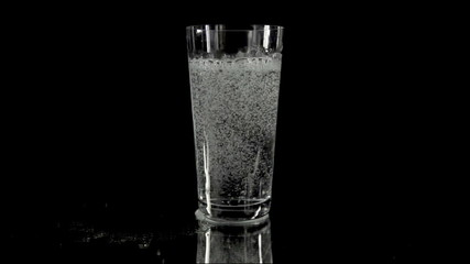 Pouring some more fizzy water into the glass in slow motion