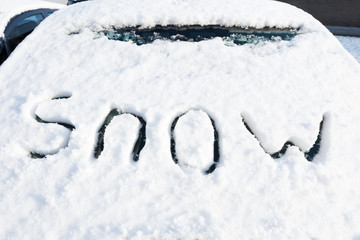Word snow written on windshield of car