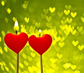 red hearts candles on yellow hearts bokeh as background