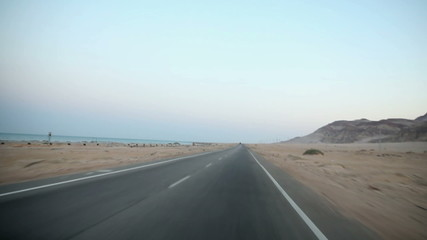 Driving on empty road by the sea in desert
