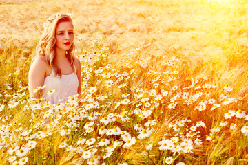 Blond girl on the camomile field