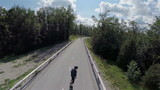 Flying over road towards forest with person on longboard