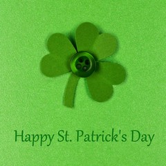Happy St Patrick Day text with handmade shamrock on green