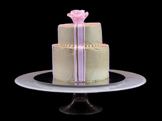 One beige cake with a pink rose isolated on black