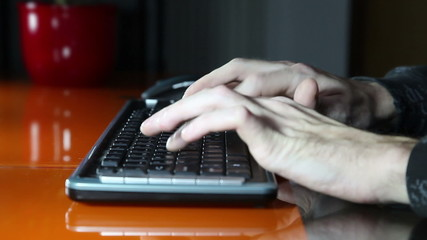 Shot of a man`s hands typing on a computer keyboard