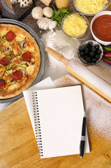 Pizza with notebook, chopping board and ingredients