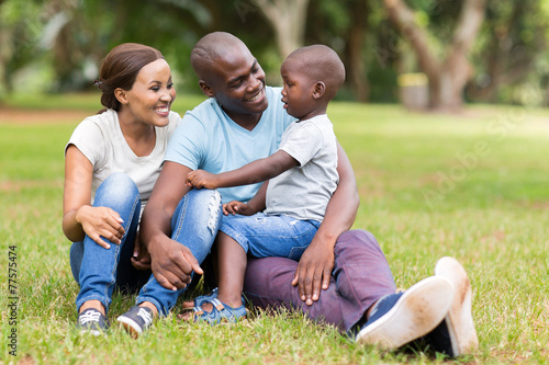 Leinwanddruck Bild young african family sitting outdoors
