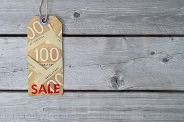 Canadian sale tag on brown vintage paper against wooden backgrou