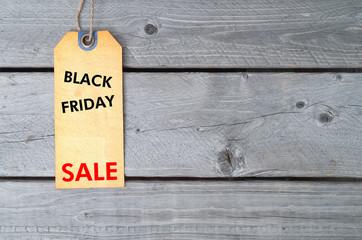 Black Friday sale tag on brown vintage paper against wooden back