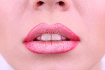 Applying lipstick on lips, on white background