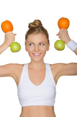 young woman with dumbbells fruits looking away
