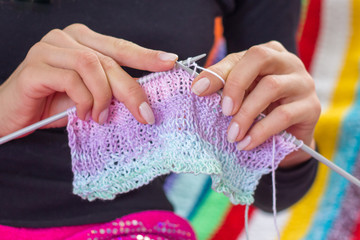 Woman knitting multicolored scarf
