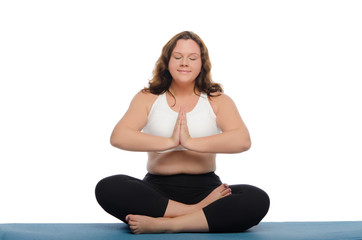 woman with overweight is meditating on mat