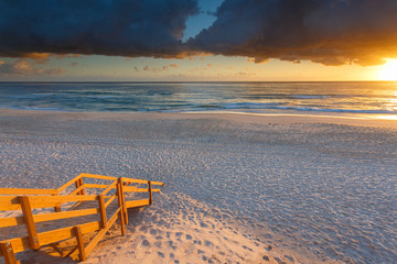 Australian beach entry with stairs in foreground at sunrise