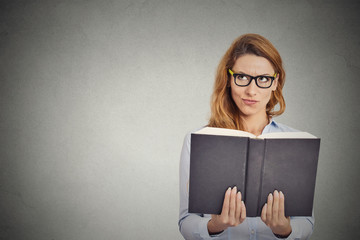 woman with glasses reading book having thought