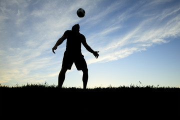 A soccer player play in back lit day time