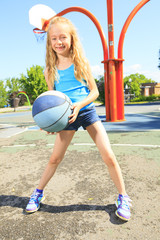A little girl play basketball with on the playground