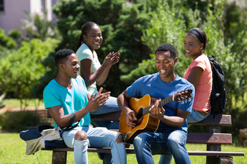 african college boy playing guitar for friends
