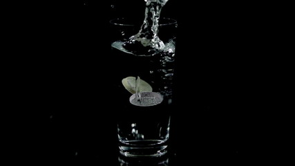 Vitamin tablets fall into a glass of water and start to dissolve