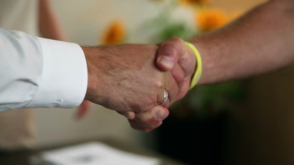 Close up of shaking hands in office