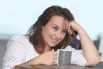 beautiful woman with a cup of drink daydreaming