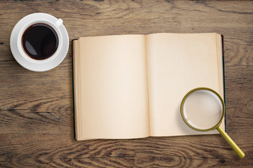 Diary or open book with loupe and coffee cup.
