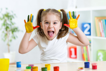 Funny kid with hands painted in colorful paint