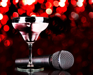 Silver microphone and cocktail on table on red lights