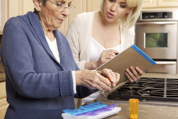 Senior Women Getting Help Organizing Her Prescription Medicine