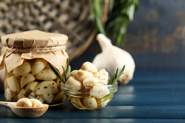 Canned garlic in glass jar on color wooden background