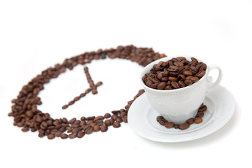 The white cup of coffee bean in front of grain clock