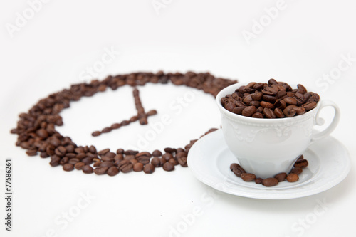 Roasted coffee beans in shape of clock and white cup