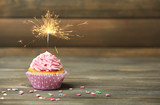 Cupcake with sparkler on table on wooden background