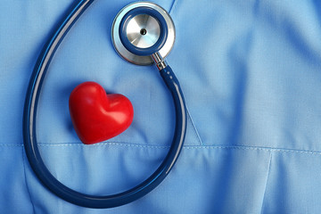 Stethoscope with heart on suit background, close-up