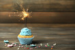 Cupcake with sparkler on table on wooden background - 77588696