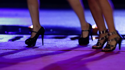 Women in miniskirts are dancing on red carpet