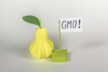"paper pear  and card with word ""GMO!"""