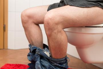 Nahaufnahme Mann sitzt auf einer Toilettenschüssel