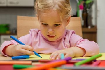 Blondes Mädchen malt konzentriert an einem Bild