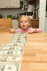 Kleines Mädchen mit vielen Dollar Banknoten auf dem Tisch