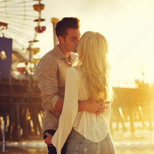 young romantic couple kissing in front of sunset in santa monica - 77592072